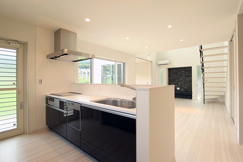 システムキッチンはアイボリー色の空間にアクセントカラーとして映えるブラックを採用しました。