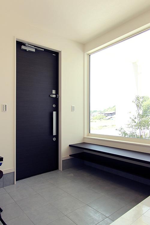 玄関は大型のFIXサッシを配してシンボルツリーを望む明るく開放的な空間としています。
