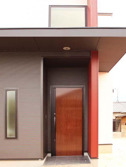 エンジの壁パネルが印象的な玄関アプローチ