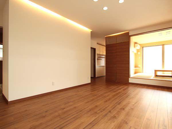 リビングルーム。一段上がった畳スペースの横には壁面収納を設置しました。