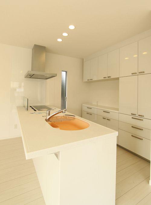 ホワイト色のキッチンにオレンジ色のシンクが映えます