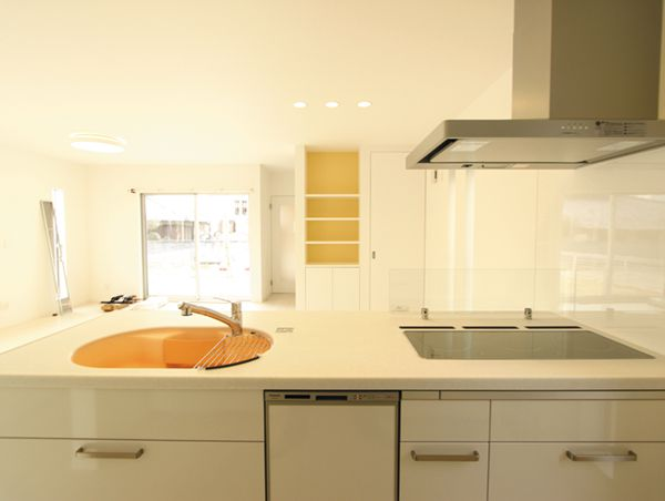 キッチンから望むリビングルーム。収納棚のオレンジ色がとってもお洒落