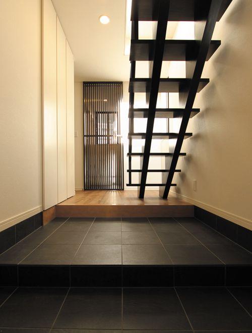 玄関正面の格子戸や壁に溶け込んだ下足箱で広々として落ち着いた雰囲気の玄関を演出。