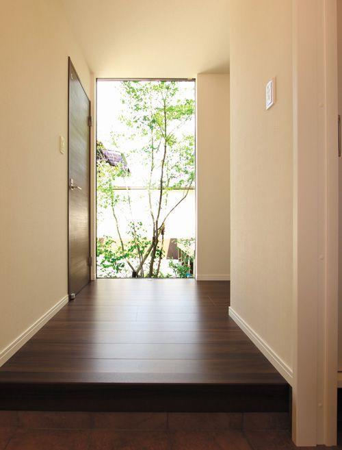 正面の大型サッシからシンボルツリーを望むギャラリーのような玄関。