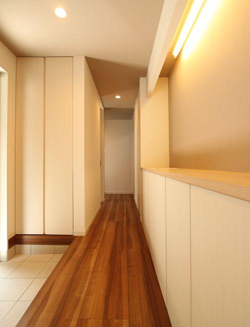 玄関はシンプルなデザインのオリジナル建具を使用した下足箱とロングカウンターでスッキリとした空間に仕上げました。