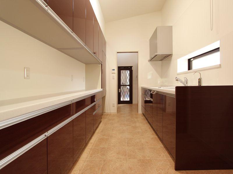 キッチンは独立タイプとし、ロングカウンター食器棚や横長窓を設置、洗面所への動線も確保しました。
