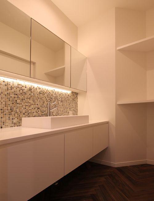 造りつけの洗面化粧台はモザイクタイルと間接照明でホテルのような雰囲気にしました。