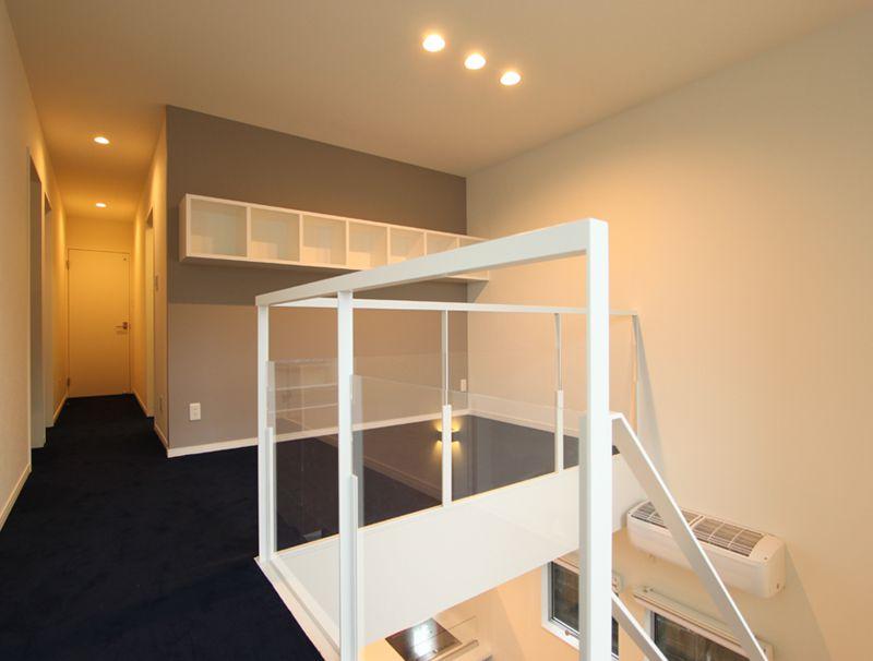 2階のフリースペースにはデザインに配慮した棚を設置。青いカーペットの床とグレーの壁でモダンな空間になっています。