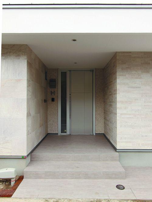 玄関アプローチはマット系シルバーの玄関ドアとアースカラーの自然石が優しい雰囲気を醸し出しています。