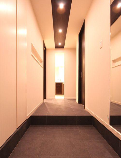 玄関は床タイルを張り伸ばし、色数を少なくすることによってシンプルモダンな雰囲気としました。