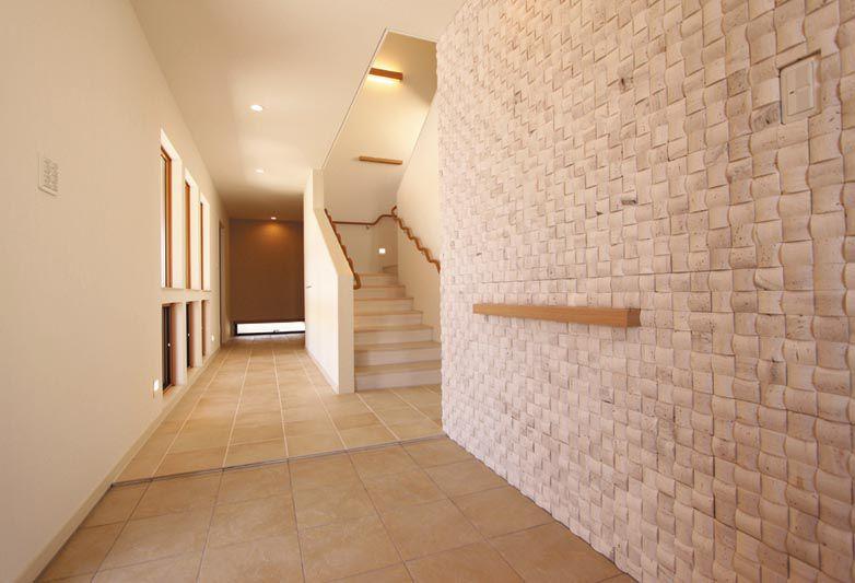足が不自由なご主人に配慮し段差のない玄関。 タイル貼りの壁の裏側はご家族専用の玄関となっています。