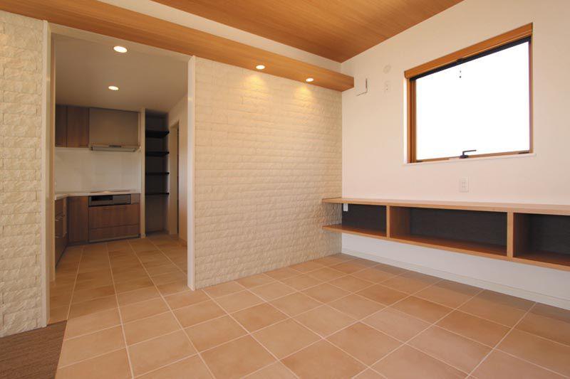 ダイニングの床はキッチンと連続したタイル貼りとし、オリジナルの家具や大型の窓を配しました。