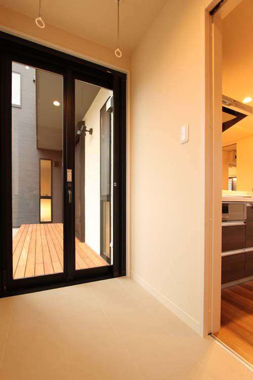 キッチンに連続した室内物干しスペース。 スライディングサッシで南面のウッドデッキをフルオープンに出来ます。
