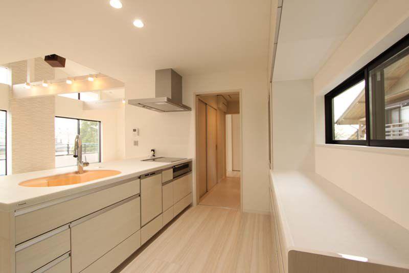 キッチン背面のロングカウンター、洗面所へと続く機能的な動線。