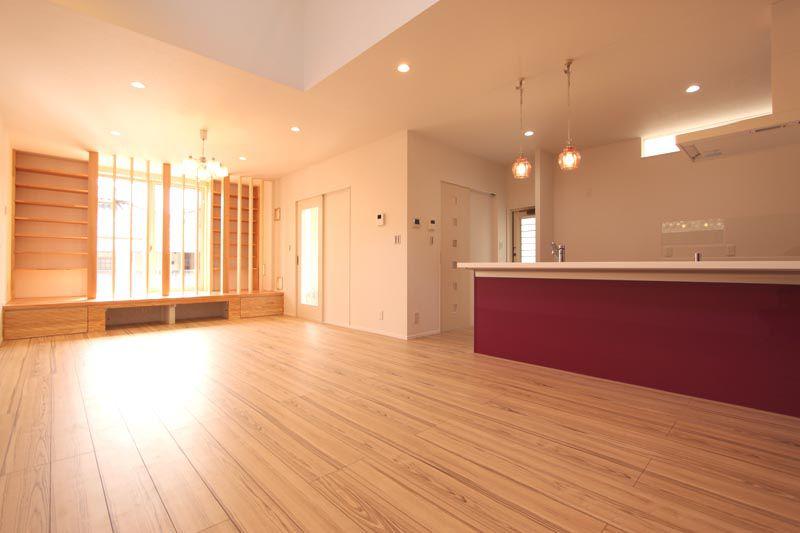 エンジ色のキッチンが映えるリビングダイニング。