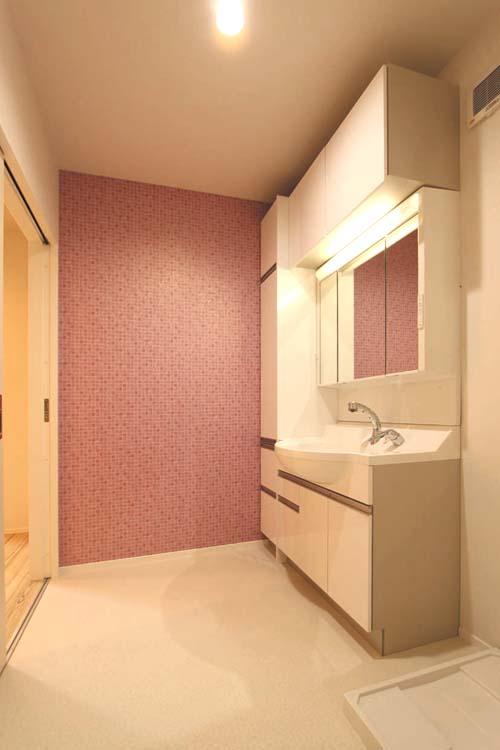 壁面をアクセントクロスであしらった明るい雰囲気の洗面脱衣室。