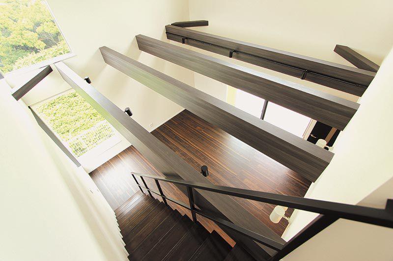 リビング吹き抜けの化粧梁とストリップ階段が存在感を演出します。