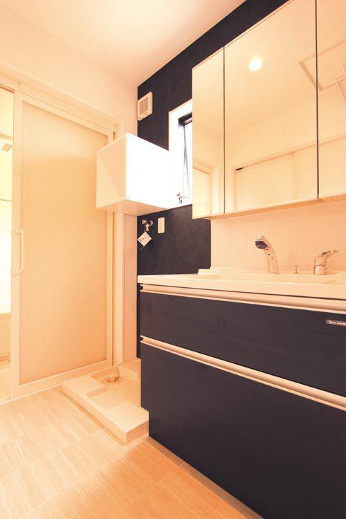 洗面化粧台と洗濯機置き場。洗濯機置場の上部にはボックスタイプの棚を配しました。