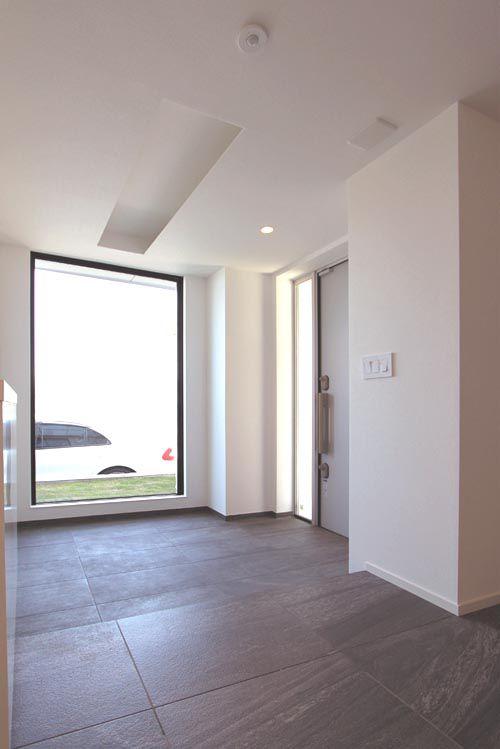 壁一面に大開口のサッシを配した、明るく広々とした大判タイル貼りの玄関。
