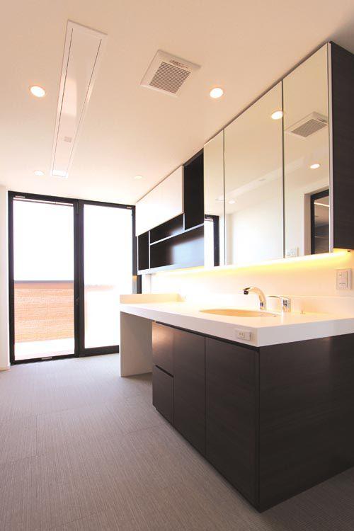 サブバルコニーに連続する洗面脱衣室にはワイドな特別注文の洗面台を配し、昇降式の室内物干しも設置しました。