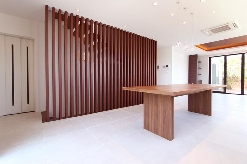 リビング配した階段沿いの木製ルーバーと住宅用エレベーター。