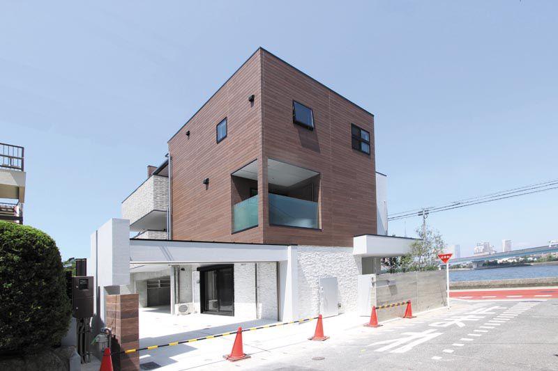 ワイドな駐車場ゲートと川と海に映える建物デザイン。