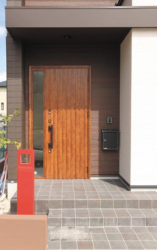 玄関ファサードには木質感漂う大型の玄関ドアとちょっと小粋なアクセントサインポストを設置。