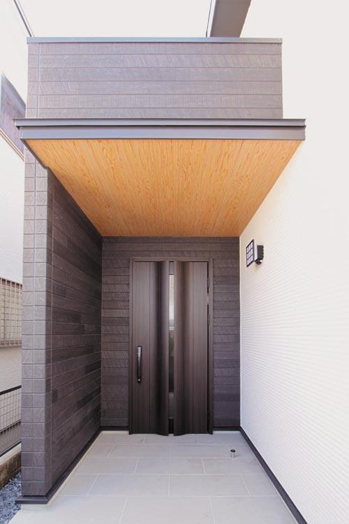 ブラックの木目調を基調とした和モダンな玄関ファサード。