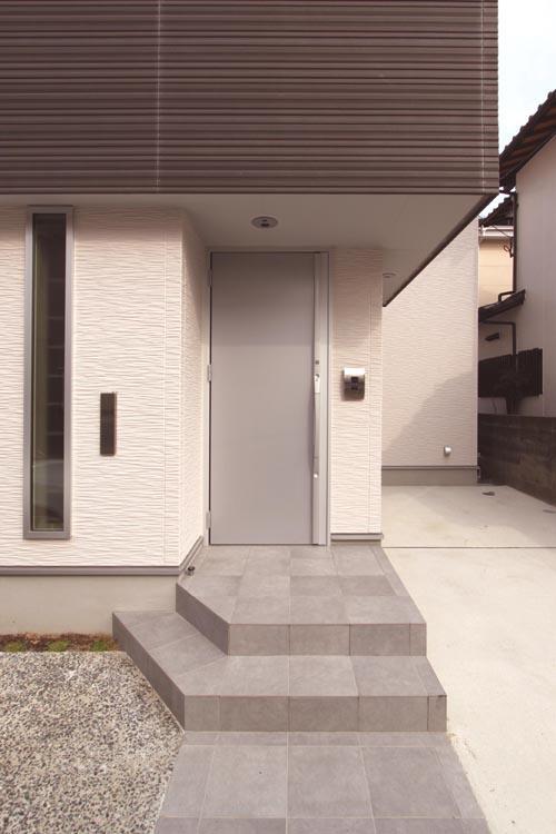 マットシルバーの玄関ドアとホワイトの壁でモダンな雰囲気を醸し出す玄関ファサード。