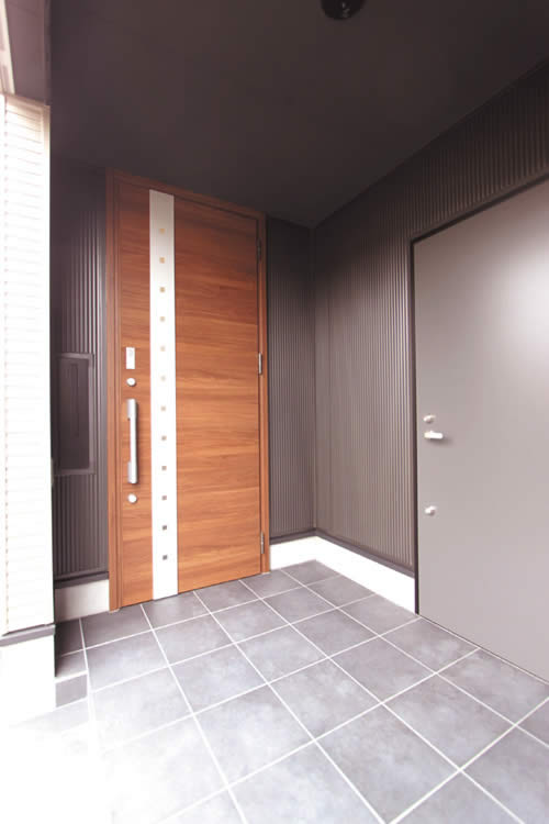 木目調のスタイリッシュな玄関ドア。ガレージ直通の出入り口を玄関横に配しました。