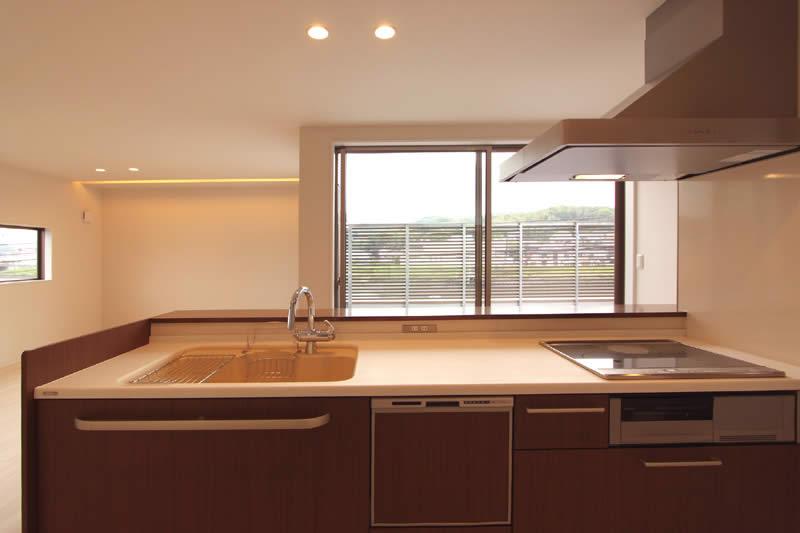 広いバルコニーを正面に見て調理できるキッチンは明るくて機能的。