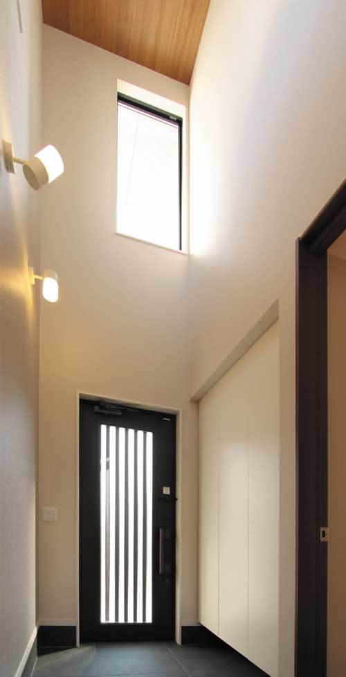 玄関ホールは吹き抜けを設けて自然光をたっぷりと採り込む開放的な空間としました。