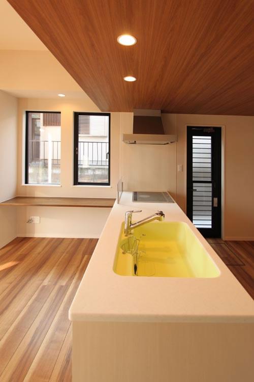 イエローの大理石シンクが特徴的な清潔感溢れる対面キッチン。