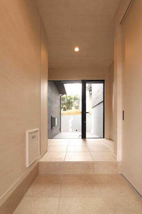 解放感のある明るい玄関はホワイトテラコッタ調のタイルをホール部分まで敷きつめました。
