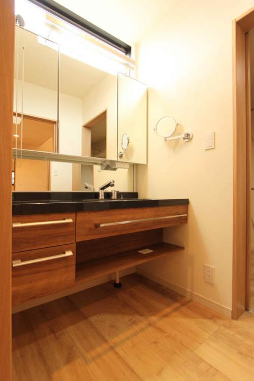 ブラックの天板や深いウォルナット調の木目をあしらった高級感のある洗面化粧台。