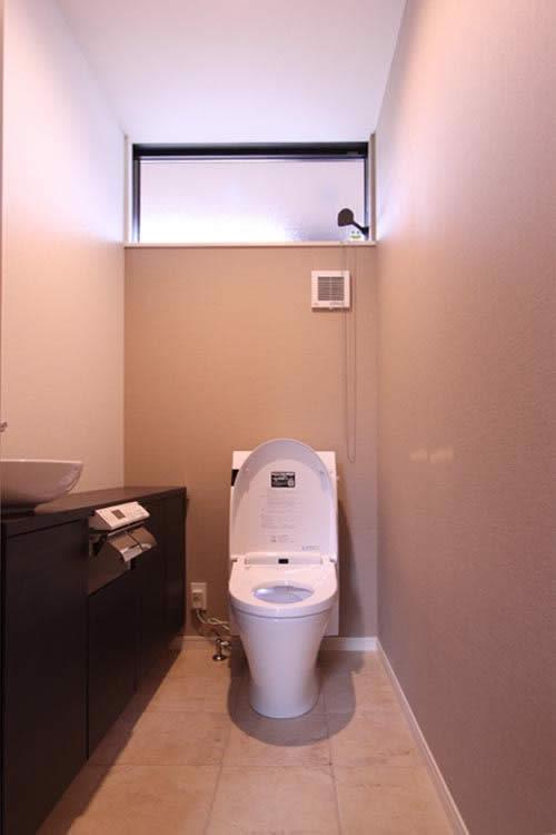 ダークブラウンの手洗カウンターキャビネットを配し、落ちついた色調でまとまた1階のトイレ。