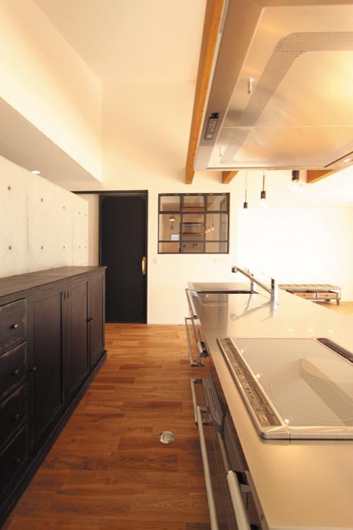 モダンなオールステンレスのキッチンやコンクリート打ち放しの壁はレトロな収納カウンターと調和して味わいのある空間としています。