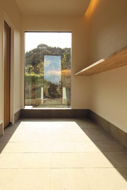 広々とした玄関にはシンボルツリーを望む壁一面の大型サッシを配し、解放感と採光を確保しました。