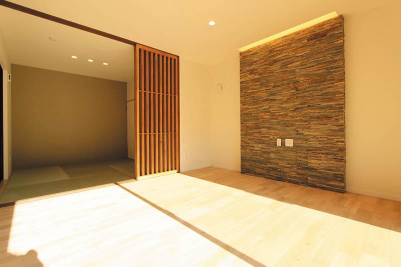 モダンテイストの和室と、壁一面の自然石が美しく調和したリビング。