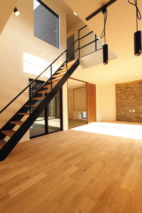 吹き抜けの鉄骨ストリップ階段にはアクセントカラーとして黒を施し、メリハリの効いたデザイン性の高いと空間としました。