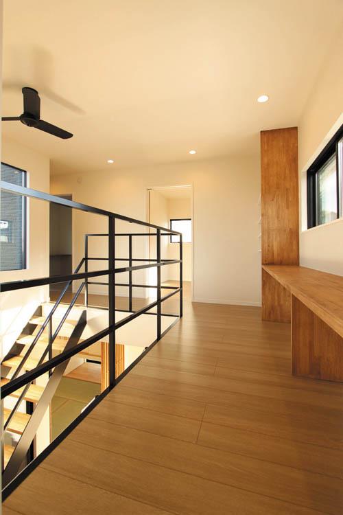 吹き抜けと連動した2階ホールは木製の多目的カウンターや黒色のデザイン手摺を配し、モダン&シックなテイストでまとめました。