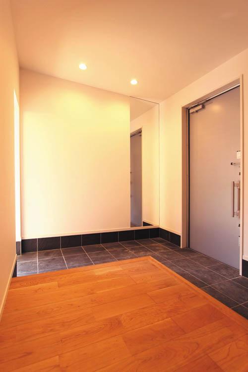 玄関ドアを開けると真正面にはガラス越しに緑の植栽が見え、隣接するのシューズルームに続くタイル貼りの土間は空間に広がりを与えます。