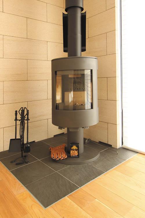 ライムストーン天然石の壁材に囲まれたデザイン性の高い薪ストーブは高級感溢れるスペースとなっています。
