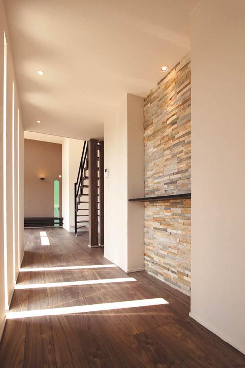 リビングとキッチンダイニングを繋ぐ広い廊下には縦スリットの窓と石ボーダーをデザインしました。