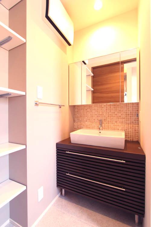 洗面化粧台は造り付けタイプを採用。壁面には人気のモザイクタイルを貼りました。