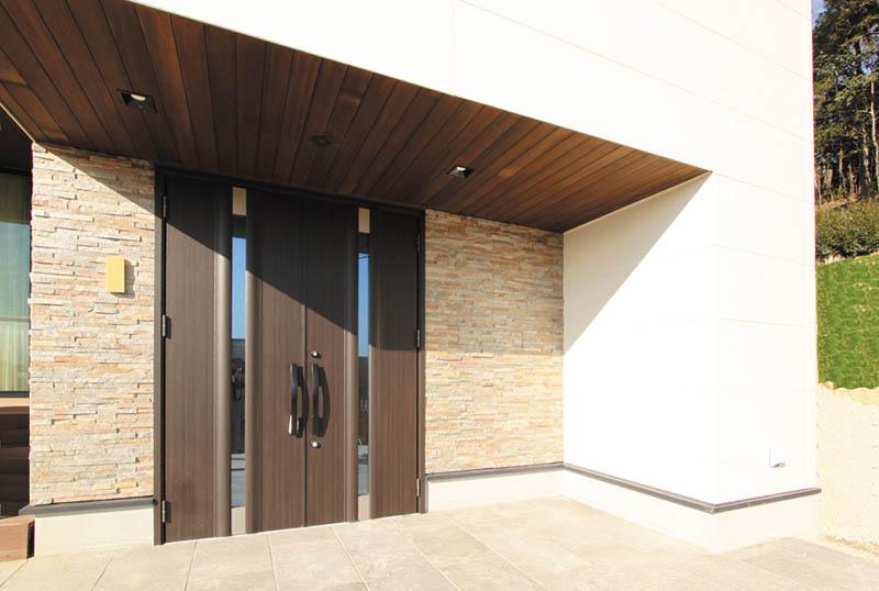 自然石ボーダーをあしらった玄関ファサード。両開きの玄関ドアが存在感を醸し出します。