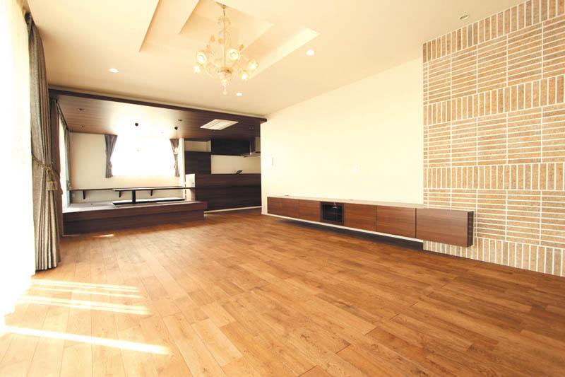 リビングは天然木のフローリングと壁面のアクセントタイルが調和したシックな空間となっています。