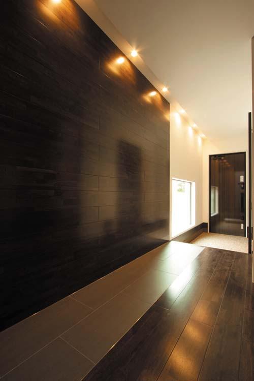 玄関~廊下の壁には木質パネルを用い、床には一部タイルを貼って、重厚な空間としました。