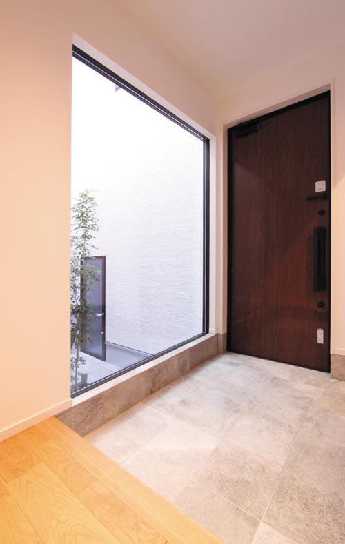 玄関にはライトコートに向けて大開口のサッシを配し、自然石調のタイルを貼って瀟洒な雰囲気を醸し出しました。